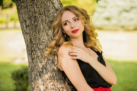 portrait of beautiful young smiling woman in red shorts posing in a park near a tree Reklamní fotografie