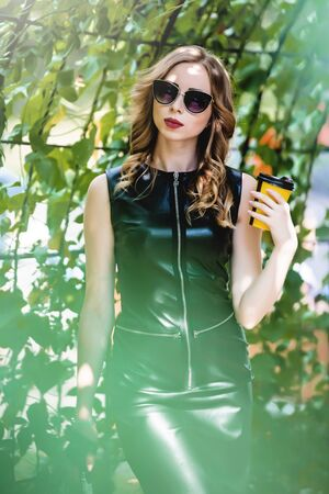 Portrait of curly woman in black skin dress posing in the garden. seductive girl