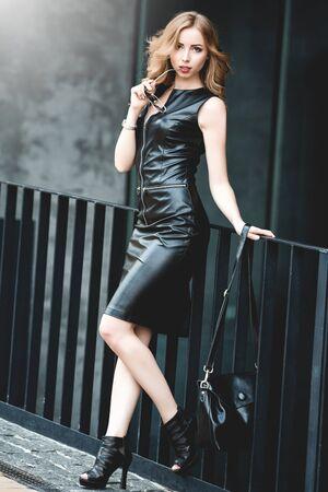 Portrait of curly woman in black dress on a street Reklamní fotografie
