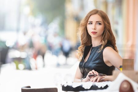 Attractive young caucasian woman sitting in street cafe, waiting for someone, having coffee, having great time. She wearing black stylish dress, 版權商用圖片