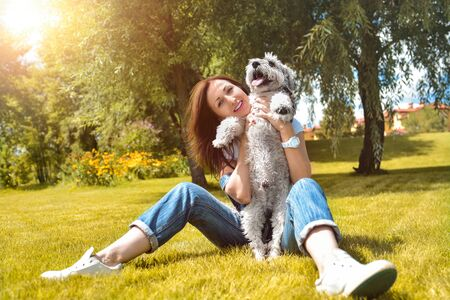 Pretty adult caucasian happy woman resting in the park on a sunny day with her beloved dog. Female lay on the grass smiling and looking at the camera Reklamní fotografie - 130767490