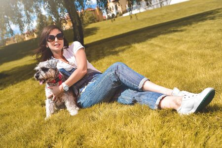 Pretty adult caucasian happy woman resting in the park on a sunny day with her beloved dog. Female lay on the grass smiling and looking at the camera Reklamní fotografie - 130767491