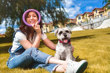 Caucasian joyful woman playing with her beloved dog in the park. The concept of love for animals. best friends. Dog breed Schnauzer Reklamní fotografie - 130767494