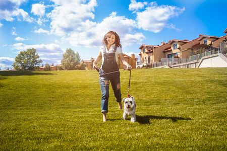 Adult Caucasian happy woman run in the park with her beloved dog Schnauzer. fun mood Reklamní fotografie - 130767496