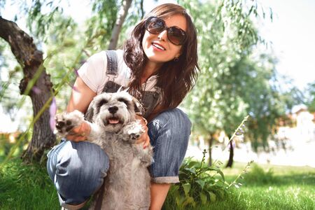 happy caucasian woman in sunglasses resting in nature with her beloved dog schnauzer.