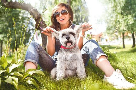 happy caucasian woman in sunglasses resting in nature with her beloved dog schnauzer. Reklamní fotografie - 130767502