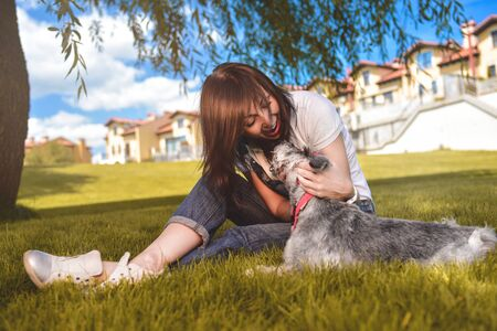 Caucasian joyful woman playing with her beloved dog in the park. The concept of love for animals. best friends. Dog breed Schnauzer Reklamní fotografie - 130767517