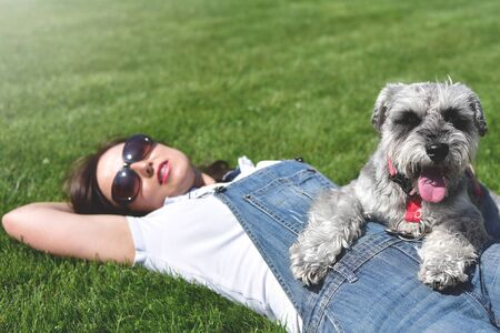 Pretty adult caucasian happy woman resting in the park on a sunny day with her beloved dog. Female lay on the grass smiling and looking at the camera Reklamní fotografie - 130767522