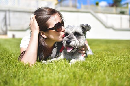 Pretty adult caucasian happy woman resting in the park on a sunny day with her beloved dog. Female lay on the grass smiling and looking at the camera