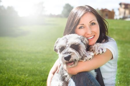 Portrait of a happy caucasian woman who hugs her beloved dog.The concept of love for animals. best friends. Dog breed Schnauzer. sunny day Reklamní fotografie - 130767524