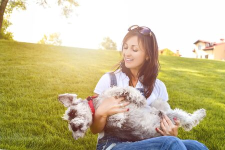 Portrait of a happy caucasian woman who hugs her beloved dog.The concept of love for animals. best friends. Dog breed Schnauzer. sunny day Reklamní fotografie - 130767525