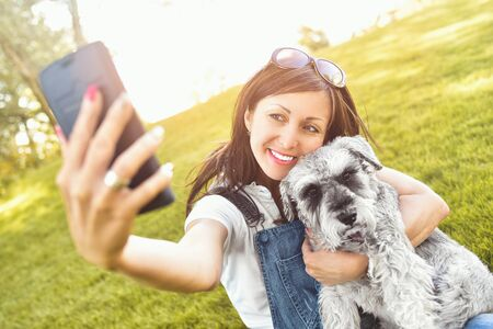 Portrait of a happy caucasian woman who hugs her beloved dog and Makes selfie with him .The concept of love for animals. best friends. Dog breed Schnauzer