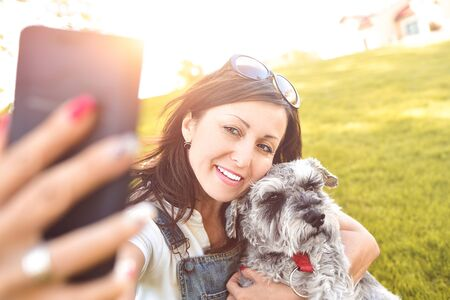 Portrait of a happy caucasian woman who hugs her beloved dog and Makes selfie with him .The concept of love for animals. best friends. Dog breed Schnauzer Reklamní fotografie - 130767633