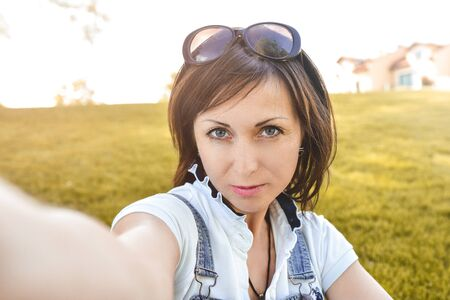 Adult caucasian woman n nature, taking selfie and walking in the evening park . selfie