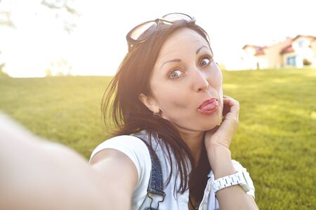 Fun Emotion, Adult woman having fun in nature, taking selfie. fun