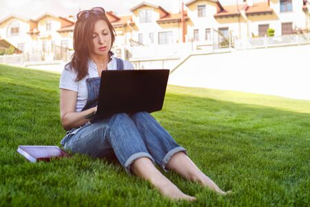 Portrait of pretty adult woman sitting on green grass in park with laptop on legs, spending summer day working outdoor, using laptop and wireless Internet for online work. Lifestyle concept.