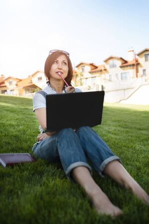 Portrait of pretty adult woman sitting on green grass in park with laptop on legs, spending summer day working outdoor, using laptop and wireless Internet for online work. Lifestyle Reklamní fotografie