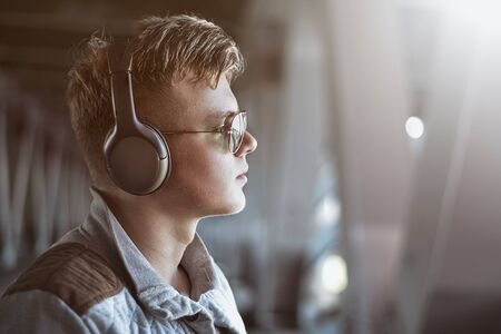 Portrait of a young stylish man listening to music with earphones . Lifestyle concept. Reklamní fotografie