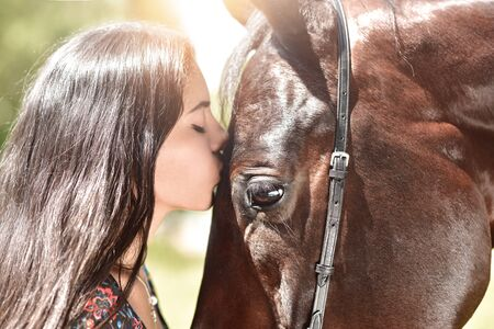 Horse and girl share an emotional moment in close up shot as they appear to kiss. Reklamní fotografie