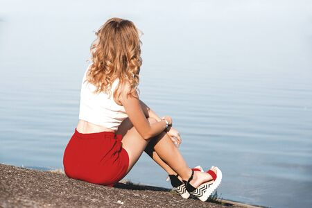 Back view of lonely caucasian girl sitting on the ground near lake at morning time Reklamní fotografie