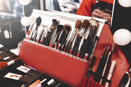 Closeup of makeup tools. Professional makeup brushes in tube, leather bag on a wooden table. Set of different objects for makeup artist in their holder. Reklamní fotografie