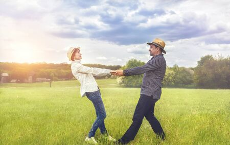 a portrait of a happy middle-aged couple holding hands in the green field.