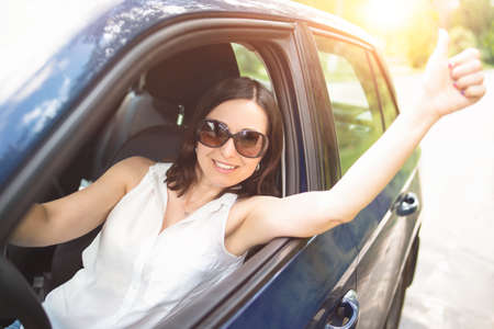 A smart looking middle-aged adult woman wearing sunglasses put her hand out the car window and raised her thumbs up. Stockfoto