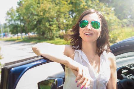 Beautiful girl is standing near her car. open the door of vehicle