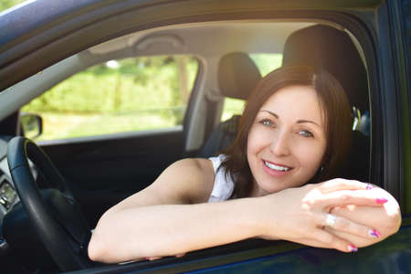 Smiling female driver looking out the car. a portrait of a smiling woman sitting in the car, looking at the camera.