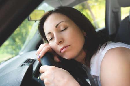 Tired woman asleep on steering wheel in her car Stockfoto