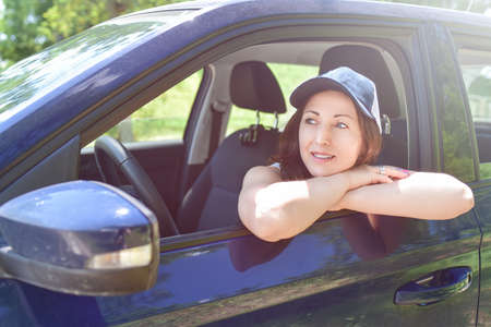 Beautiful adult happy woman driving her car in summer day Stockfoto