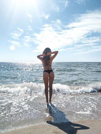 back view of slim young woman posing in bikini near the sea on resort
