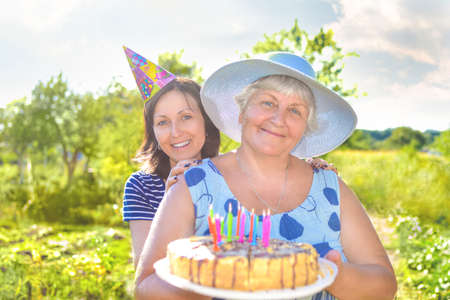 Grandmother's birthday, who with a smile, together with her daughter in the village and holds a birthday homemade cake. Stockfoto