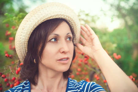 Image of beautiful middle-aged woman wearing straw hat laughing and looking at camera while walking in summer park