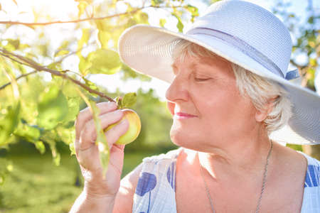 Happy senior woman blooming and enjoying flowers in the garden under apple tree