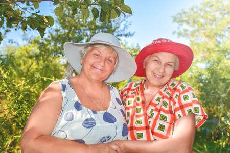 Walk in the garden. Two retired women best friends walk happily in the garden.