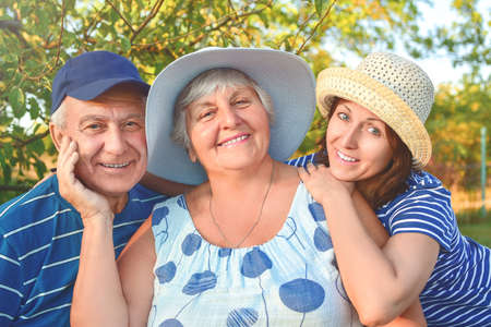 Beautiful senior couple is sitting on the bench in the park with their adult daughter. Grandma and grandpa are hugging and smiling. Real love and family relationship photo. Generations concept. Фото со стока