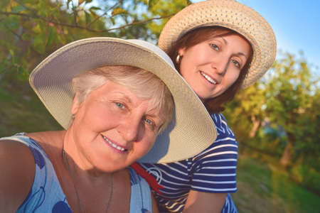 portrait of a happy elderly woman hugging her daughter and makes selfie at the park Stockfoto