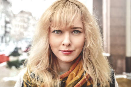 Urban portrait of a beautiful smiling Caucasian girl with blond curly hair looking at the camera Standard-Bild