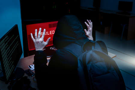 Internet criminal hacker trying to hack into corporate servers arrested by police at night. Portrait of a surrendered computer hacker who raised his hands under a flashlight. failed system hack
