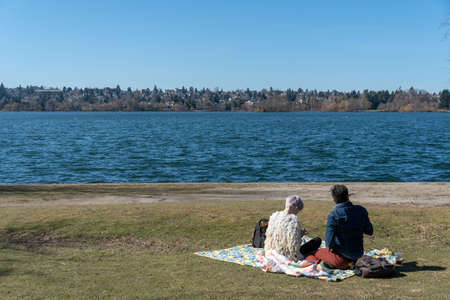 Seattle, Washington - 2019-03-17 - Couple having a picnic in Greenlake as Spring begins in Seattle 免版税图像