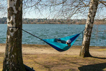 Woman reading a book in a hammock hanged from a couple of trees in Greenlake as Spring begins in Seattle