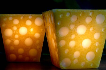 two candles in the shape of yellow cheese shine with a fire light in the dark