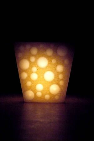 single one candle in the shape of yellow cheese shine with a fire light light reflection