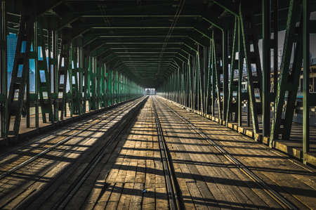 railway tram bridge over the river green iron trusses and wood in Warsaw Poland