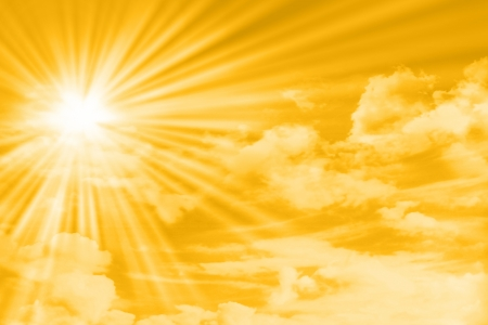 yellow sky with clouds, sun and sun rays