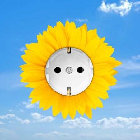 Sunflower combined with a convenience outlet on blue cloudy sky symbolizing sun energy photo