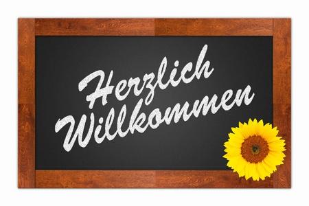 willkommen: Herzlich Willkommen (Welcome) written in chalk on a blank blackboard with sunflower on wooden frame, isolated on white background