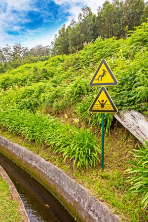 singn: Caution signs near a Levada (water supply) of the Island Madeira Stock Photo