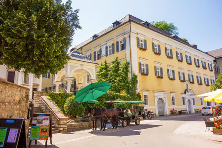wolfgang: St. Wolfgang, Austria - June 23, 2014: The center of the village with a fiacre in front. Sankt Wolfgang is a famous travel destination, located at the Wolfgangsee. Editorial